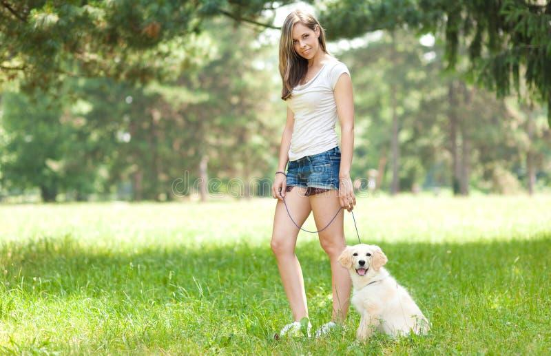 Mujer joven que camina hacia fuera su perro imagenes de archivo