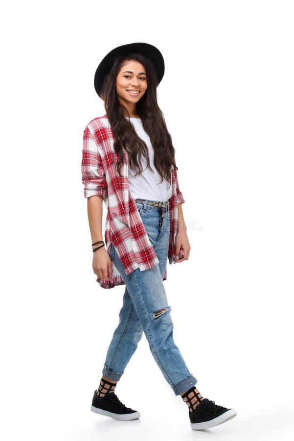 mujer joven que camina hermosa en camisa de tela escocesa elegante imagen de archivo libre de regalías