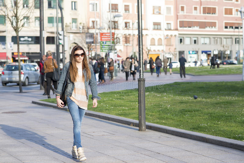 Mujer joven que camina a través de la muchedumbre en la calle. fotografía de archivo