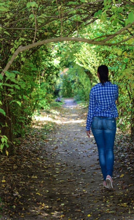 Mujer joven que camina a través del parque fotografía de archivo