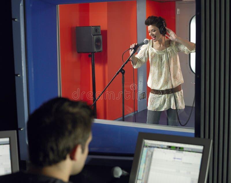 Mujer joven que canta con el técnico In Foreground del estudio imagen de archivo libre de regalías