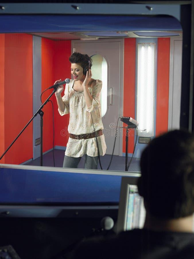 Mujer joven que canta con el técnico In Foreground del estudio fotografía de archivo