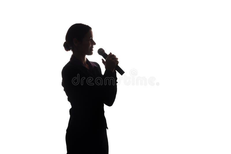 Mujer joven que canta en el micr?fono fotografía de archivo