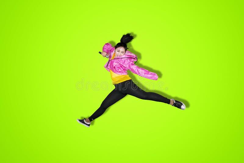 Mujer joven que canta y que salta en estudio foto de archivo