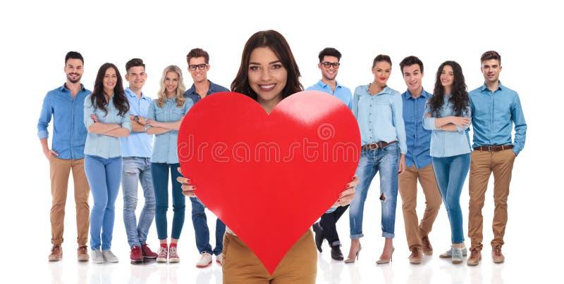 Mujer joven que celebra día del ` s de la tarjeta del día de San Valentín con su grupo casual foto de archivo libre de regalías