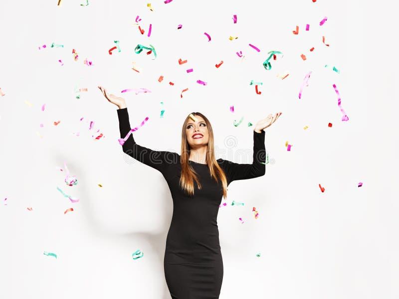 Mujer joven que celebra, el caer del confeti foto de archivo