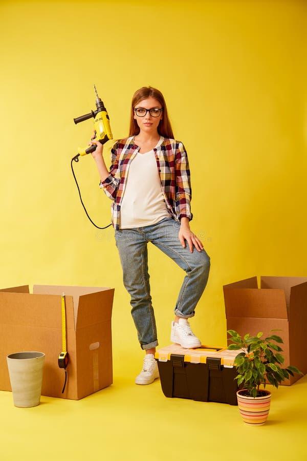Mujer joven que celebra un taladro, colocándose entre las cajas para moverse estudio fotos de archivo