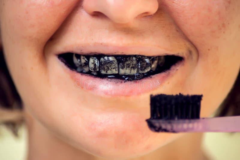 Mujer joven que cepilla sus dientes con una goma de diente negra con carbón de leña activo, y el cepillo de dientes negro Ci?rres foto de archivo libre de regalías