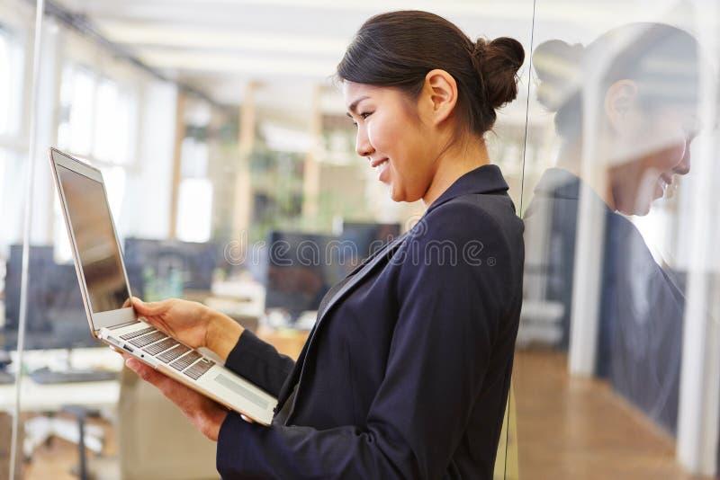Mujer joven que charla con el ordenador portátil imagenes de archivo