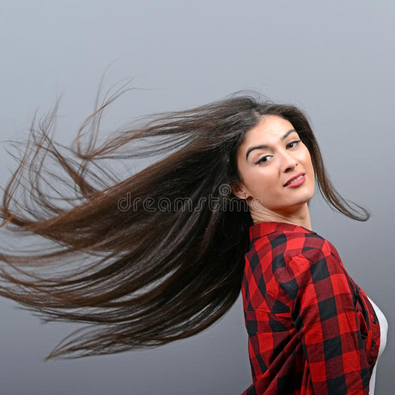 Mujer joven que chasquea su pelo y que presenta contra fondo gris fotografía de archivo