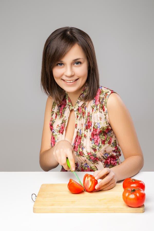 Mujer joven que cocina en la cocina imagenes de archivo