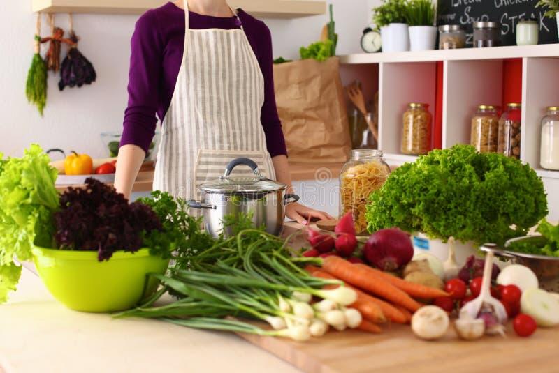 Mujer joven que cocina en la cocina Alimento sano fotografía de archivo