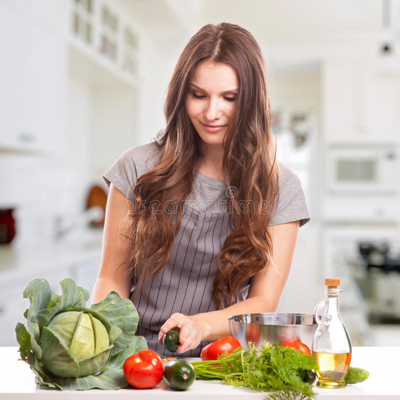 Mujer joven que cocina en la cocina Comida sana - imágenes de archivo libres de regalías