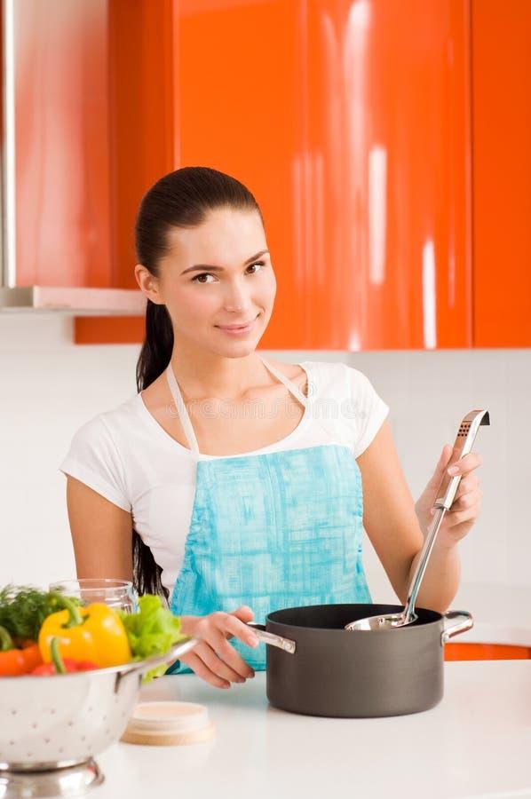 Mujer joven que cocina en la cocina, probando la sopa imágenes de archivo libres de regalías