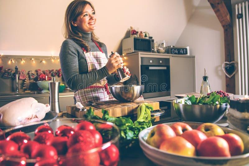 Mujer joven que cocina en la cocina Comida sana para el pato o el ganso relleno la Navidad imagenes de archivo