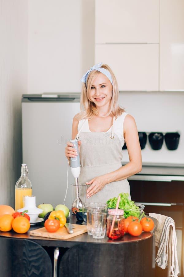 Mujer joven que cocina en la cocina imagen de archivo libre de regalías