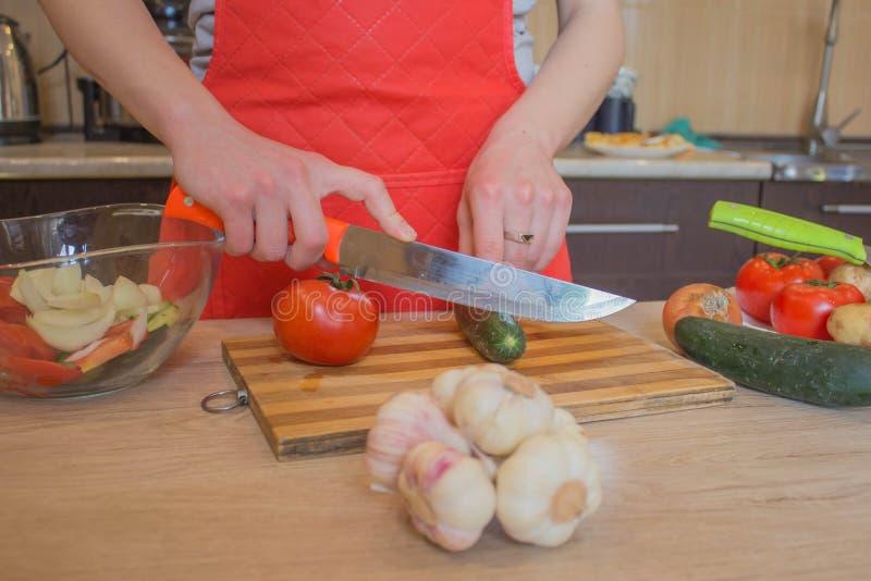 Mujer joven que cocina la comida sana en la cocina Cocinando la comida sana en casa Mujer en la cocina que prepara veh?culos Cort fotografía de archivo libre de regalías