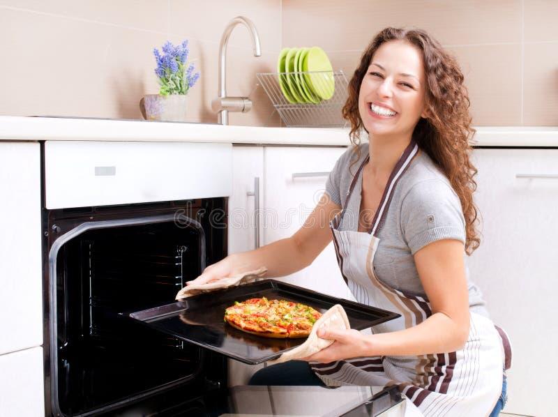 Mujer joven que cocina la pizza