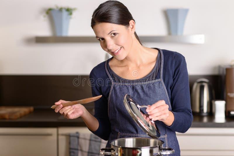 Mujer joven que cocina sobre la estufa foto de archivo