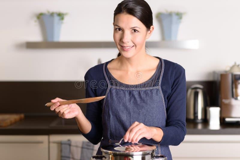 Mujer joven que cocina sobre la estufa fotografía de archivo