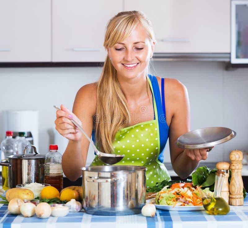 Mujer joven que cocina verduras fotos de archivo