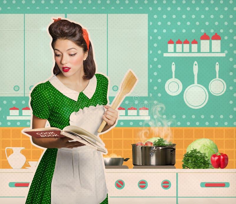 Mujer joven que cocina y que lee el libro del cocinero de la receta en su cocina imágenes de archivo libres de regalías