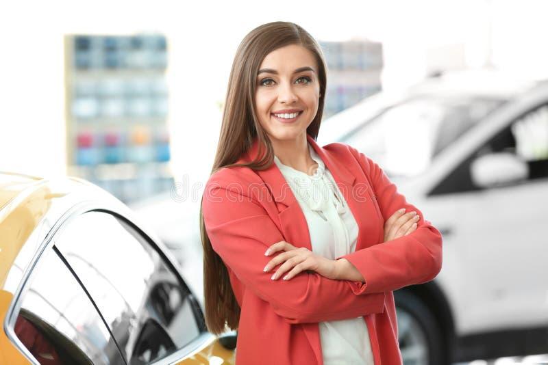Mujer joven que coloca el coche cercano foto de archivo