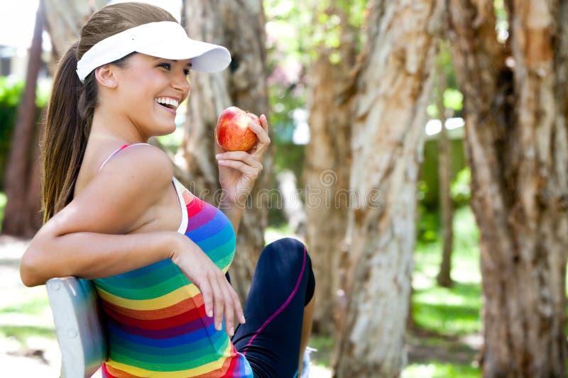 Mujer joven que come Apple en banco de parque imagen de archivo libre de regalías