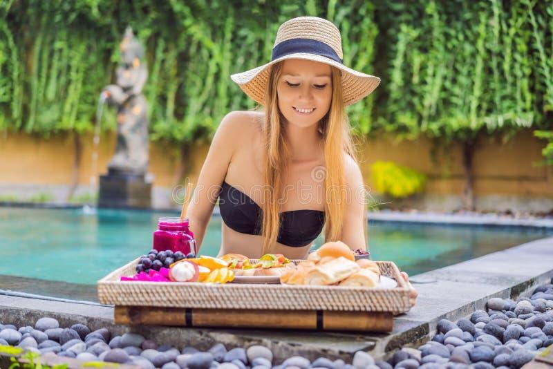 Mujer joven que come el desayuno en una bandeja con la fruta, bollos, bocadillos del aguacate, cuenco del smoothie por la piscina imagenes de archivo