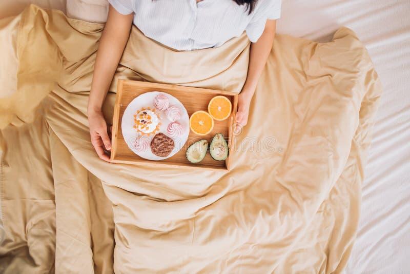 Mujer joven que come el desayuno sano en cama fotografía de archivo libre de regalías