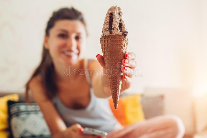 Mujer joven que come el helado del chocolate en el cono que se sienta en el sofá en casa fotos de archivo