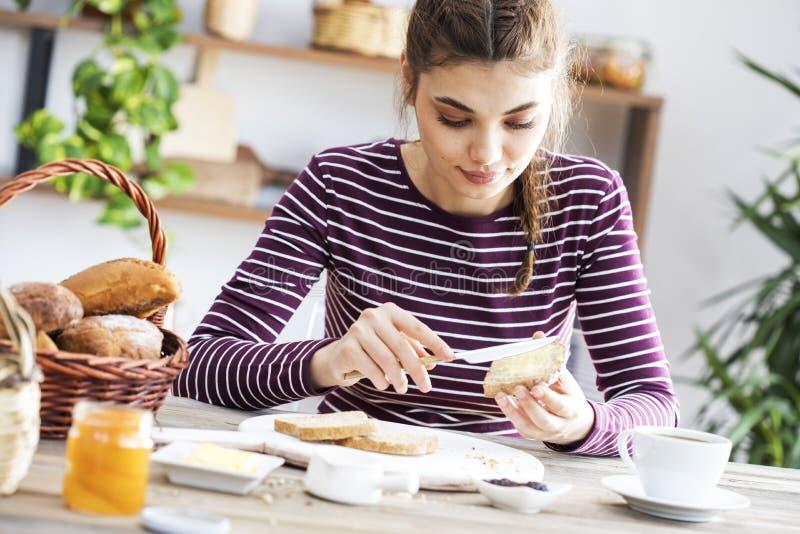 Mujer joven que come el pan con mantequilla foto de archivo