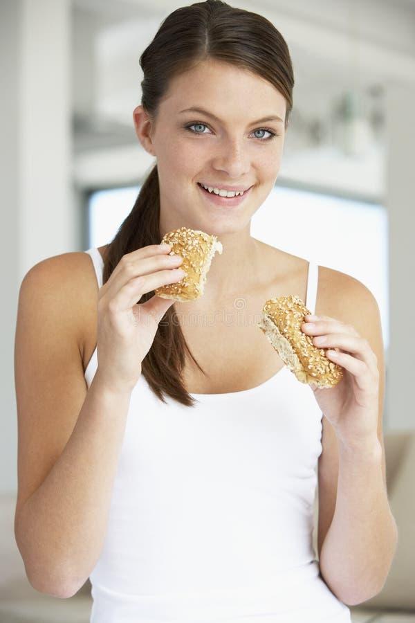 Mujer joven que come el rodillo de pan de Brown fotos de archivo