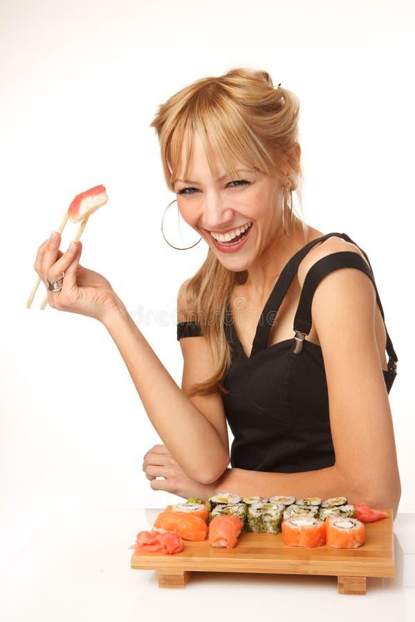 Mujer joven que come el sushi con los palillos foto de archivo