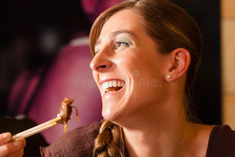 Mujer joven que come en restaurante tailandés imagenes de archivo