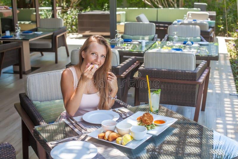 Mujer joven que come en restaurante tropical al aire libre fotos de archivo libres de regalías