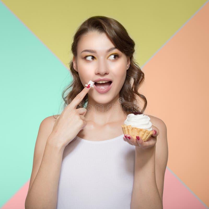 Mujer joven que come feliz un postre dulce Para traer un finger en una crema dulce a una boca Fondo brillante colorido foto de archivo libre de regalías