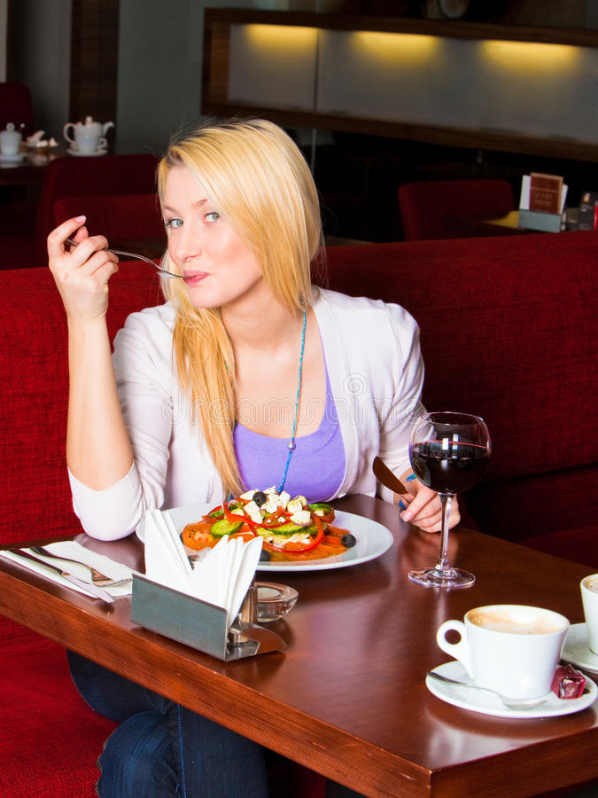 Mujer joven que come la cena imagen de archivo libre de regalías