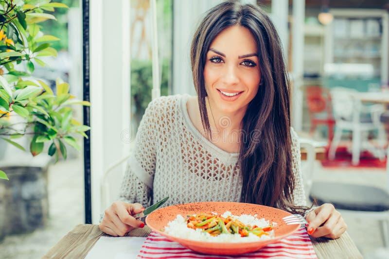 Mujer joven que come la comida china en un restaurante, teniendo su lunc foto de archivo libre de regalías