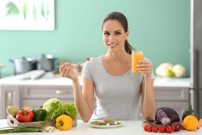 Mujer joven que come la ensalada de las verduras frescas y que bebe el jugo en cocina fotos de archivo