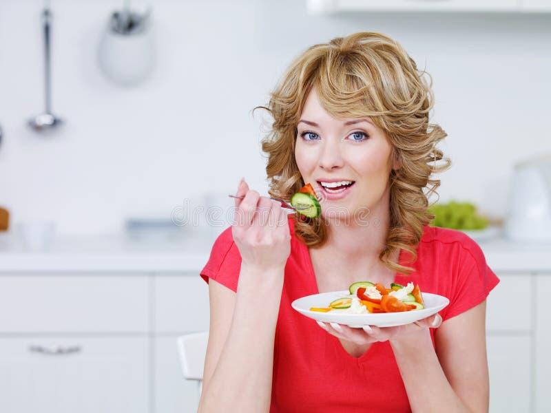 Mujer joven que come la ensalada en la cocina foto de archivo libre de regalías