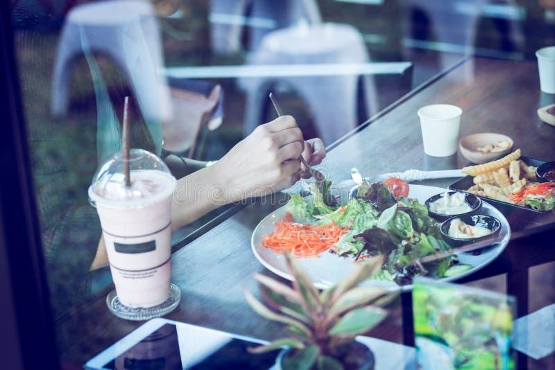 Mujer joven que come la ensalada y la bebida en café foto de archivo libre de regalías