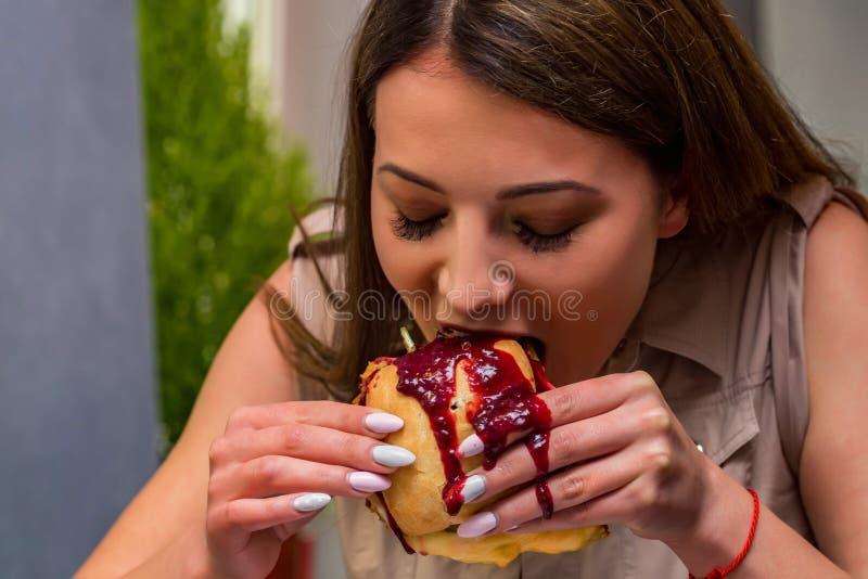 Mujer joven que come la hamburguesa en restaurante Cierre encima de la cara y de las manos cubiertas en salsa imágenes de archivo libres de regalías