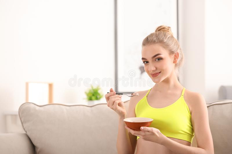 Mujer joven que come la harina de avena en casa Concepto de la comida de la dieta imagenes de archivo