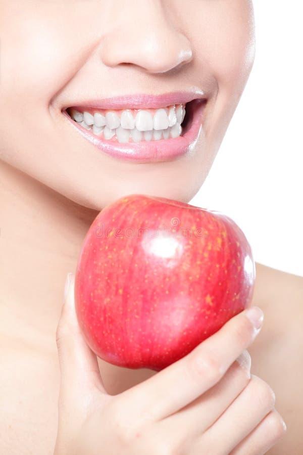 Mujer joven que come la manzana roja con los dientes de la salud imagen de archivo