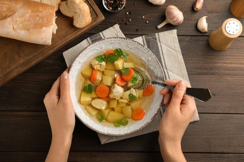 Mujer joven que come la sopa de pollo hecha en casa en la tabla imagen de archivo