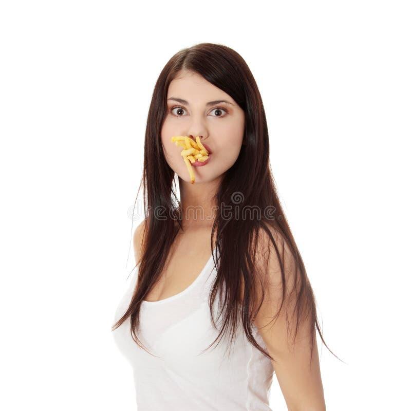 Mujer joven que come las fritadas imagen de archivo