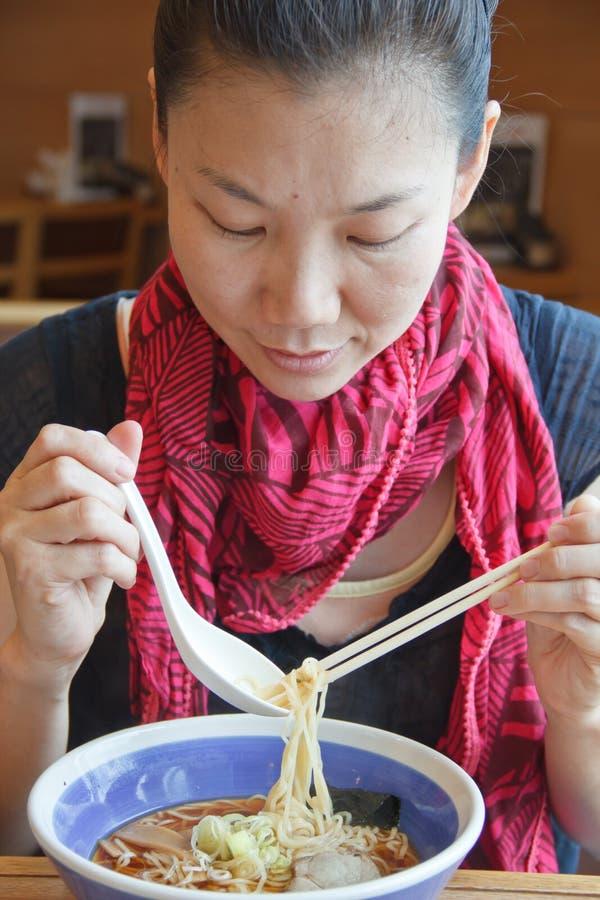 Mujer joven que come los tallarines. foto de archivo libre de regalías