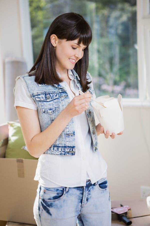 Mujer joven que come los tallarines en casa foto de archivo libre de regalías