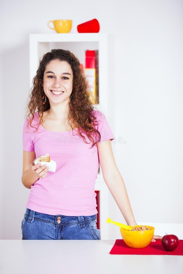 Mujer joven que come su desayuno fotografía de archivo libre de regalías